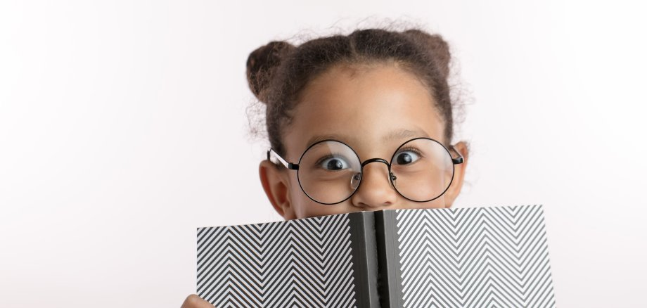 clever little girl with hairbunds and round glasses hiding behind the notepad